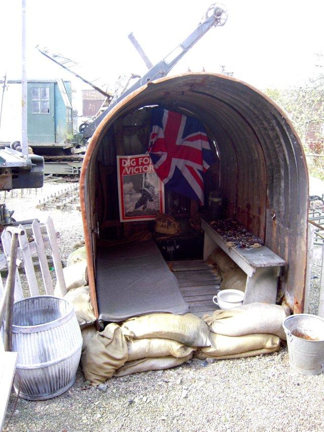Anderson shelter med grävskopor bakom